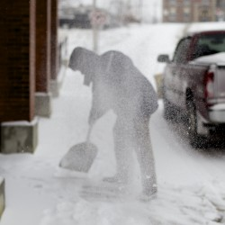 Mark Perry shovels snow away from the front of his office on Columbia Street Thursday morning in Bangor.
