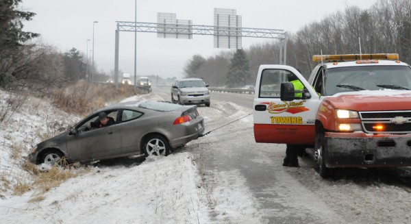 A tow truck pulls out John Arbo's vehicle from the ditch after he lost control on the slush-covered road and slid from the off-ramp between I-395 and Route 202. Arbo was not injured, and there was some minor damage to his car. Police were dealing with many similar accidents as the morning snow turned to rain and froze on the roadways.