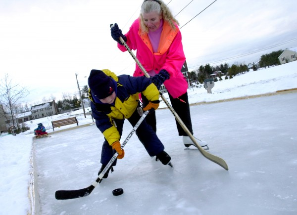 Dawn Ortonward and her son Doogie, 6, play ice hockey on their homemade ice rink in front of their house in Brewer in January 2002.