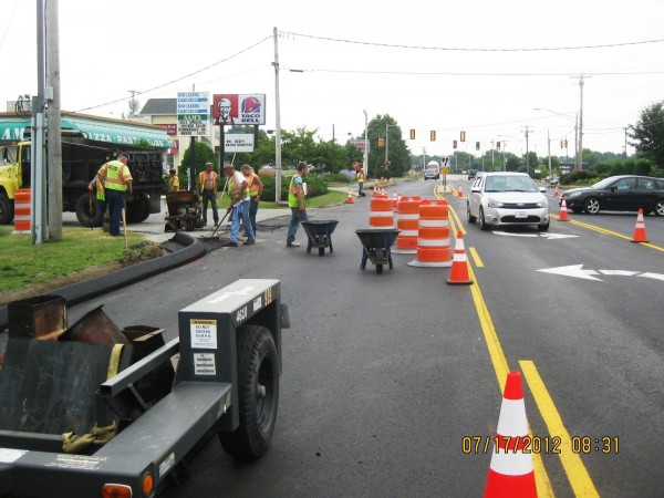 Workers with local contractor Harry C. Crooker & Sons, Inc. repave lanes in July 2012 at the Cook's Corner interchange in Brunswick. The work was made possible with both state and local funds under a new Maine Department of Transportation Municipal Partnership Initiative.