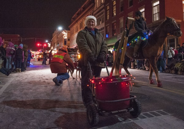 With her jaunty red bucket in tow, Sandy Oliver cares for the equine needs of the Someday Farm in the Festival of Lights parade in downtown Bangor on Saturday.