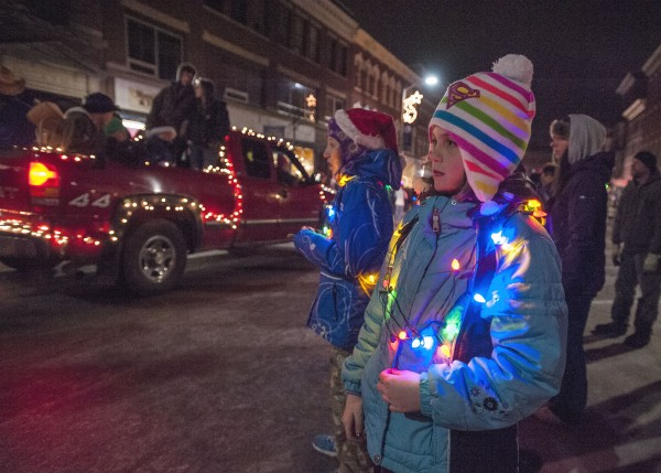 Bailey watches with her family from the curb along Main Street as the Festival of Lights parade passes by in downtown Bangor on Saturday.