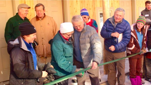Rolande and Clem Begin of Carrabassett Valley cut a ribbon at the opening celebration of the Maine Huts & Trails Stratton Brook Hut on Dec. 12, 2012. The Begins funded the construction of the alpine lodge, which is located 1,880 feet above sea level between Sugarloaf and Bigelow mountains in western Maine.