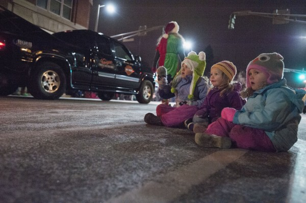 Emma, Callie and Addie sit at the curb and watch as the Festival of Lights parade passes along State Street in downtown Bangor on Saturday.