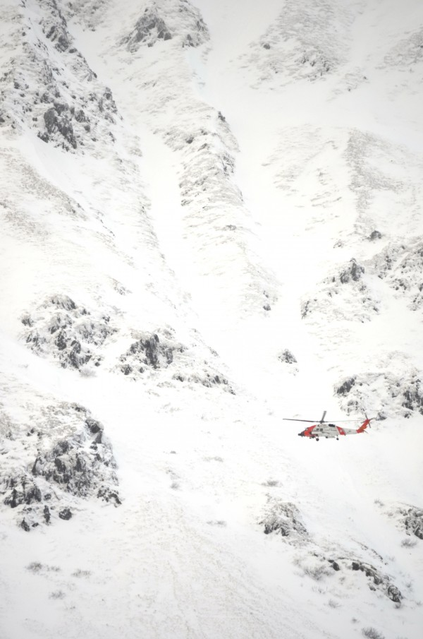 A Coast Guard helicopter searches the terrain on Mt. Barometer in Kodiak, Alaska, for signs of a missing hiker and Coast Guard crewman from Hollis Center. Derek Russell's body was found on the mountain Tuesday afternoon.