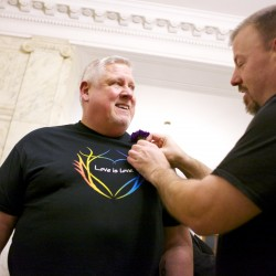 Michael Snell (left) receives a boutonniere from Steven Bridges before waiting in line to get married at Portland City Hall Friday evening.