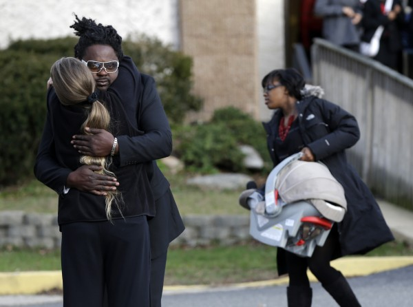 Mourners hug Wednesday after leaving the church where Jovan Belcher's funeral was held in Dix Hills, N.Y. Several hundred mourners gathered for the funeral of Kansas City Chiefs linebacker, who shot and ki