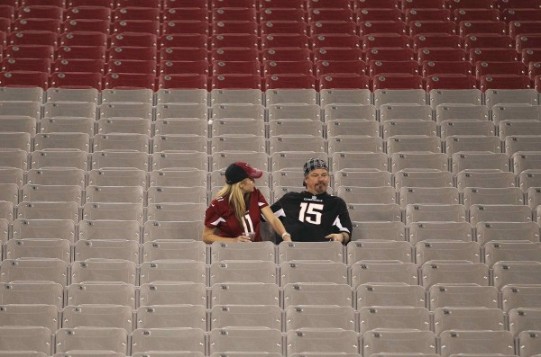 Dejected Arizona Cardinals fans sit in the stands after a 28-13 loss to the Chicago Bears during an NFL football game in Phoenix, Arizona, on Dec. 23, 2012.