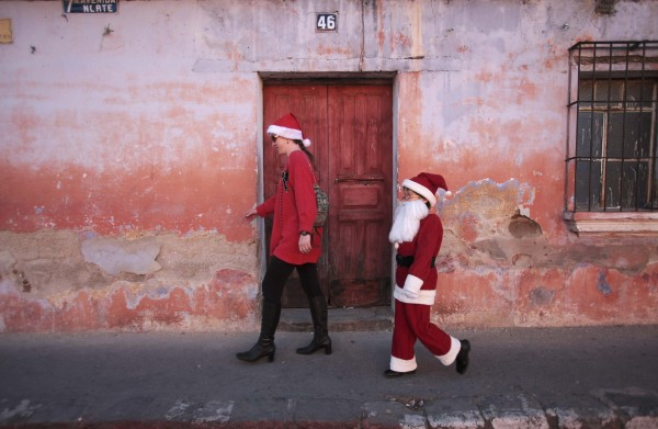 Alexander, 9, dressed as Santa Claus, walks beside his mother in Antigua, about 26 miles outside of Guatemala City, on Dec. 23, 2012.