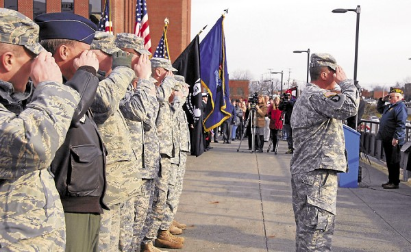 Current and former members of the Maine Air National Guard and Maine Army National Guard salute during the playing of the National Anthem at the Pearl Harbor Day ceremonies held in Bangor on Friday, Dec. 7, 2012.
