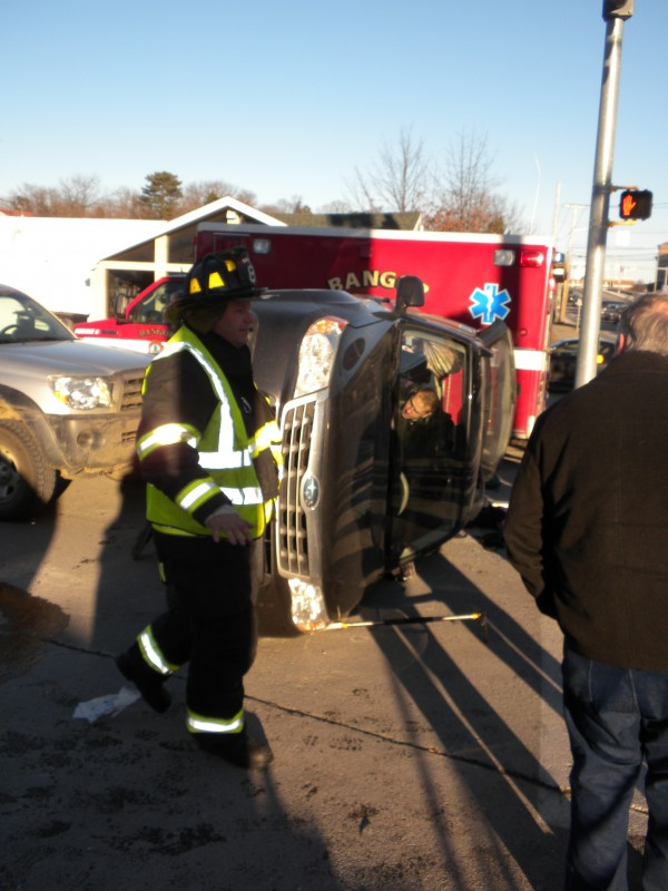 A Bangor firefighter asks onlookers to step back from the scene of a rollover at the corner of State and Otis street on Saturday, Dec. 15, 2012, while police Officer Doug Smith removes personal items from the inside the Subaru Forester. The SUV and a Chevy minivan collided at about 2:30 p.m. and the impact smashed the front end of the minivan and rolled over the SUV onto its side, trapping the female driver inside for a few minutes.