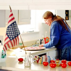 Elizabeth Tremblay makes pizza at her Poland home. &quotWhen you don't like what your government is doing, you hang your flag upside down in silent protest,&quot she said.