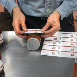 Phillip McFarland puts labels on jars of marinara sauce him and his wife produce at the Coastal Farms and Foods facility in Belfast.