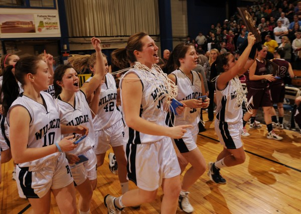 Members of the Presque Isle girls' basketball team parade their Eastern Maine Class B trophy around the floor of the Bangor Auditorium after beating No