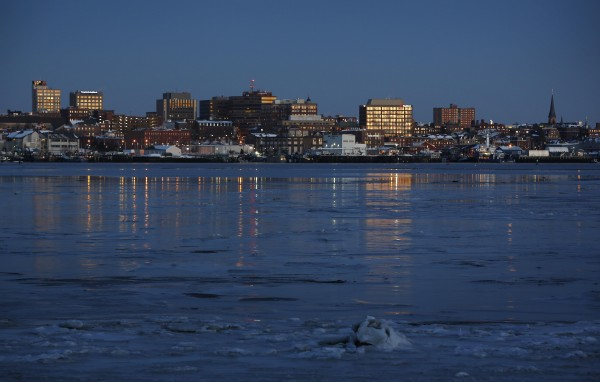 Office buildings reflect the first light of day across the partially frozen in Portland Harbor as viewed from South Portland, on Wednesday, Jan. 2, 2013