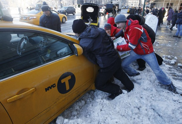Passersby help push a taxi out of a snow drift in New York on Saturday.