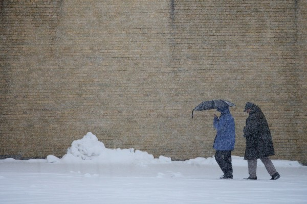 A man and a woman trudge through the wet snow on Myrtle Street in Portland on Sunday, Feb. 24, 2013.