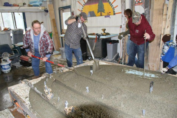 Adam Meyer (center) works with other volunteers at his Cutler warehouse to settle and smooth a concrete mixture for the base of a memorial to honor the victims of the Sandy Hook Elementary School tragedy in Newtown, Conn.