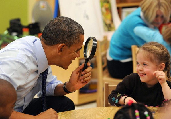 President Barack Obama uses a spy glass to play with a young girl at College Heights Early Childhood Learning Center in Decatur, Georgia, Thursday, February 14, 2013.