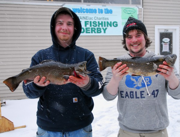 Tony Jipson of Bangor and Tommy Tardiff of Holden show off a pair  of Brook Trout they entered in the Maineiac Charities Ice Fishing Derby Saturday. In the Brook Trout category, Jipson's fish took first place, weighing 4.45 pounds and measuring 18.7 inches long. Tardiff placed second as his tipped the scales at 3.85 pounds and 19.37 inches long. The picture was taken outside Dunn's hangar on Beech Hill Pond in Otis, which was the official weigh station for the derby, but the fish were caught at Lower Springy Pond in Otis.