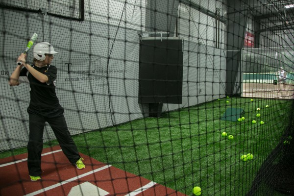 Softball player Ashley Gatt takes batting practice with the virtual pitching machine at Sluggers Baseball & Softball Training Facility in Brewer on Friday, Feb. 1, 2013. Sluggers hosted an open house to show off the new training facility.