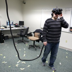 "Third-year master's student Chris Bennett walks around with a virtual reality headset at the Virtual Environment and Multimodal Interaction Laboratory at the University of Maine in Orono on Friday, Feb. 8, 2013. Students and researchers at the lab have been working on virtual reality programs to help the visually impaired, firefighters in smoke-filled rooms, and others ""see"" buildings through augmented reality."