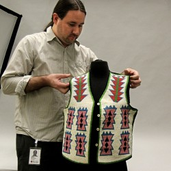 Justin McCarthy, of the Burke Museum of Natural History and Culture, adjusts the display of the American Indian beaded vest that was given to the museum by Goodwill in Seattle.