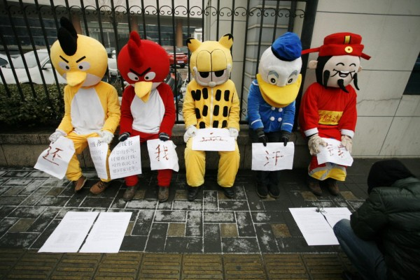 Migrant workers dressed up as Angry Birds (from left), Garfield, Donald Duck and the Chinese God of Wealth during a sit-in protest to demand their salaries outside the China National Radio headquarters in Beijing on Jan. 31, 2013. The five migrant workers, whose salaries had been defaulted by various companies after working at several construction sites in Zhangjiakou of Hebei province, came to Beijing in order to raise public awareness and get help, local media reported. The Chinese characters on the papers read, &quotGive me back my hard-earned money.&quot