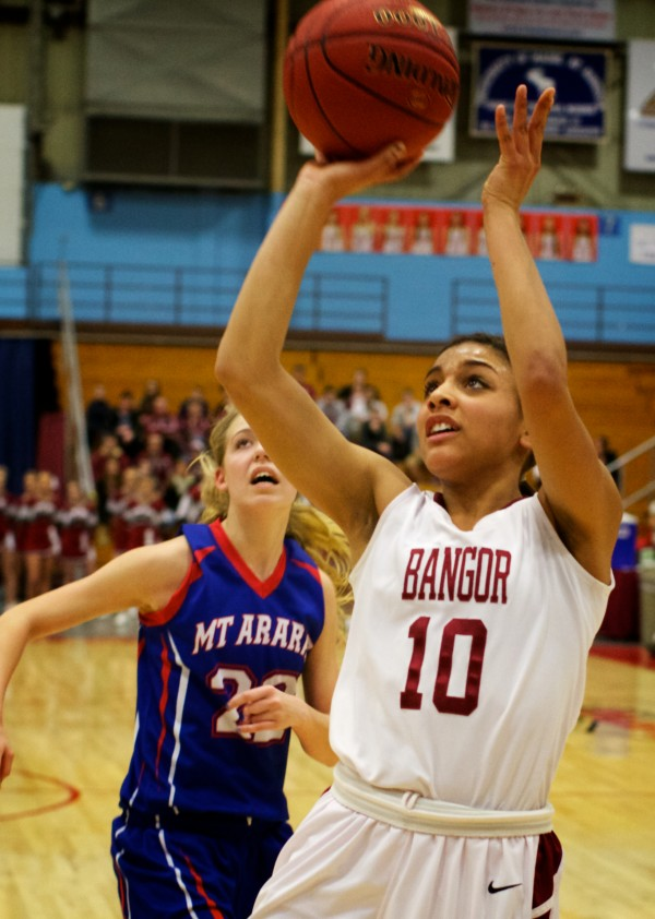 Bangor High School forward Denae Johnson (right) shoots Wednesday at the Class A Eastern Semifinal basketball game in Augusta.