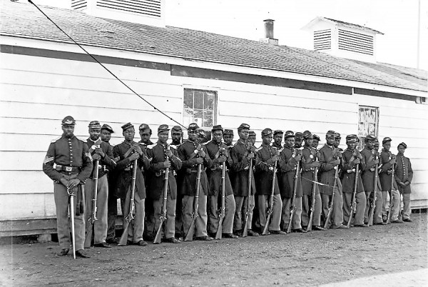 Black soldiers assigned to Co. E, 4th United States Colored Troops, proudly form outside a barracks. As the Army created new black regiments, many Maine officers and non-commissioned officers sought promotion to the available officers' slots. Federal law stipulated that only white officers could command black soldiers.
