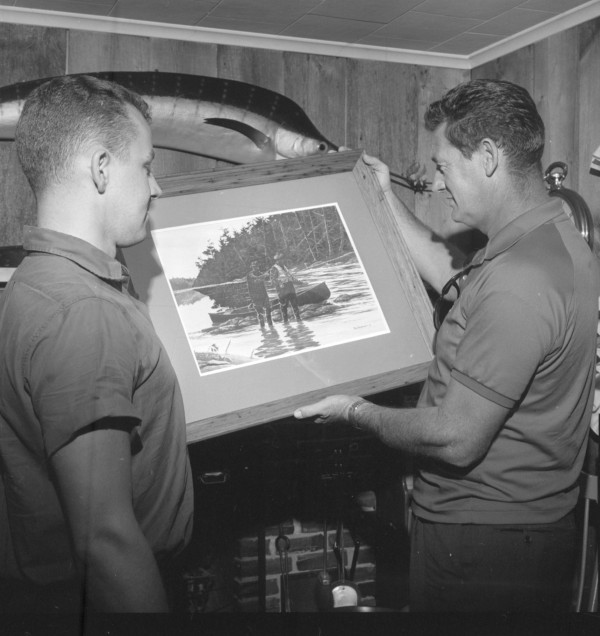 Ted Williams (right) admires a painting by Tom Hennessey of the Bangor Daily News. The painting depicts Williams on one of his Atlantic salmon fishing trips to Canada's Miramichi River. Hennessey presented the work to Williams in Bangor on Sept. 4, 1965.