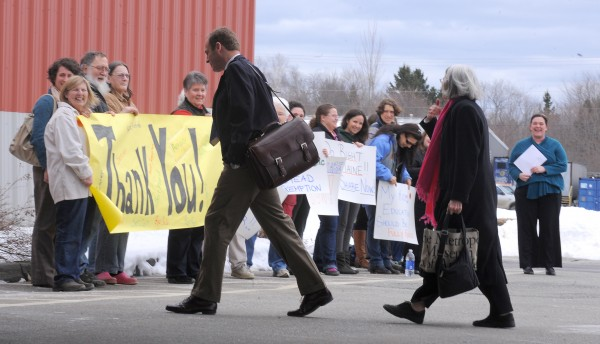 Maine State Reps. Mike Carey (foreground, left) and Peggy Rotundo walk past a group lead by the Maine People's Alliance  expressing their opposition to the proposed budget cuts by Gov. Paul LePage at Jeff's Catering in Brewer on Monday. Read the story here.