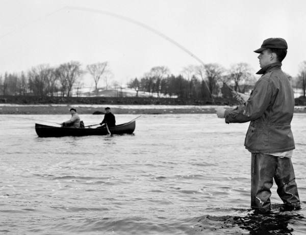 Tom Hennessey of Bangor tries his luck at the Bangor Salmon Pool on the opening day of fishing on April 1, 1960, while Dr. Frank Gilley and well-known salmon angler Guy Carroll cast from a boat. There were no reports of any salmon taken during the day's fishing.