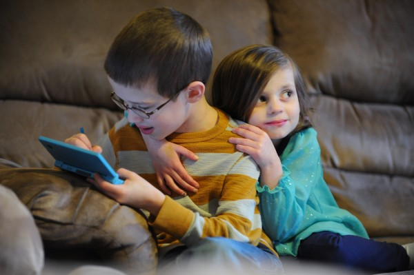 Lucas Rudnicki plays with his video game as his little sister Maggie hugs him at the family's Levant home on Friday. Lucas will donate some of his bone marrow to help his little sister, who suffers from a rare illness, Diamond Blackfan anemia, a disorder that prevents her body from generating red blood cells.