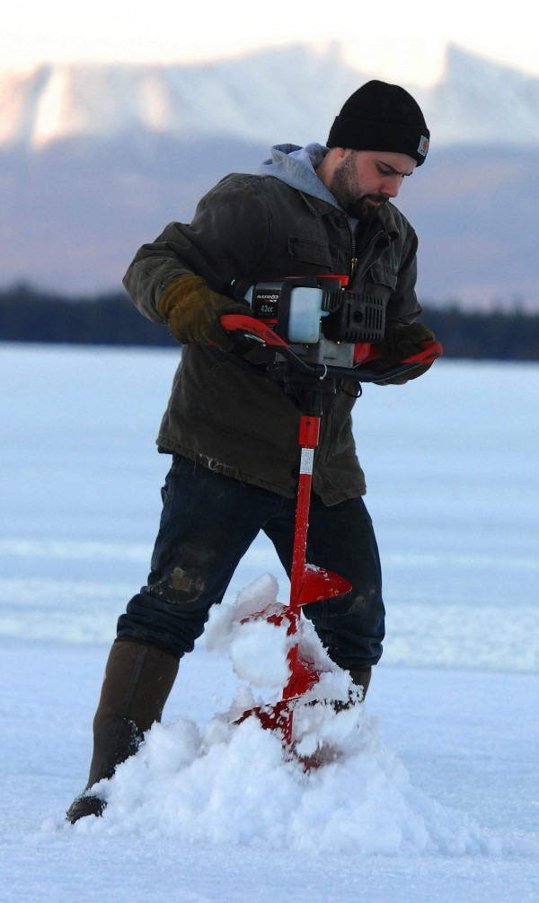Nick Elliott of Corinth, drills through some 25 inches of ice Saturday, clearing the way for an evening of cusk fishing on Upper Jo Mary Lake. Mount Katahdin looms in the background. Photo taken March 9, 2013.