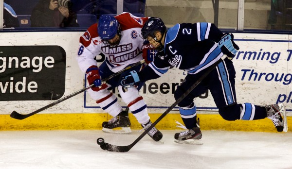 Captains Mike Cornell (right) of the University of Maine and Riley Wetmore of the University of Massachusetts Lowell scuffle for the puck in the second period Thursday night, March 14, 2013, in Hockey East quarterfinal action in Lowell, Mass.