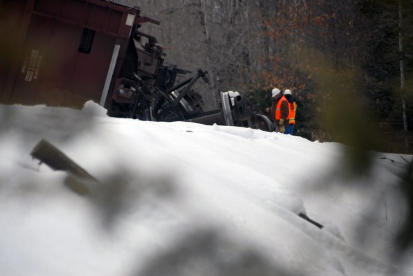 Workers from Pan Am Railways and the Maine Department of Transportation inspect a tipped-over freight car at a train derailment in Mattawamkeag on Thursday, March 7, 2013.
