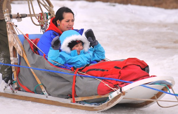 Sophia Galvan, 6, of Tampa, Fla., raises her hands as she rides in the dog sled with her mother Yolanda at the Hermon Mountain ski area Wednesday. Sophia and her family have spent the past week in Maine with the help of the Make-A-Wish Foundation that made her wish of seeing snow, building a snowman and going snowtubing come true. She is fighting nasopharyngeal rhabdomyosarcoma, a form of cancer which involves soft tissue tumors in children.