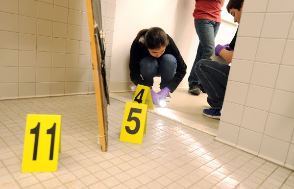 Kaylyn Larkin shines a light on a footprint as Jack Dalton prepares to roll a gel pad to lift the print for evidence during their mock crime scene at the Veazie Community School on Thursday. The &quotcrime&quot being investigated is a robbery at a tattoo parlor (the girls locker room) where illegal card games were being played after hours and gambling money was stolen.