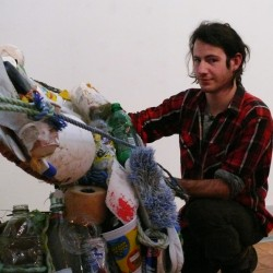Phinn Onens works on the sculpture he created from marine debris.