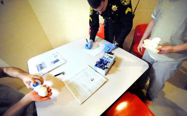 Cpl. Travys Fecteau issues razors and a squirt of shaving cream to trustees in the Androscoggin County Jail during one of his overnight 12-hour shifts.