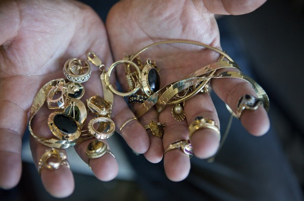 Lou Rosas holds his late mother's gold jewelry in his apartment in San Jose, Calif., on Friday, April 19, 2013. Rosas wants to sell it, but not while the price of gold is low.