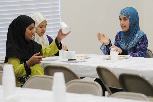 Muslim girls play a game with cups as Muslim and non-Muslim woman share a meal at the Islamic Center of Maine in Orono on Saturday after prayer. The Center hosts the put luck to encourage non-Muslims to learn more about the Islamic faith.