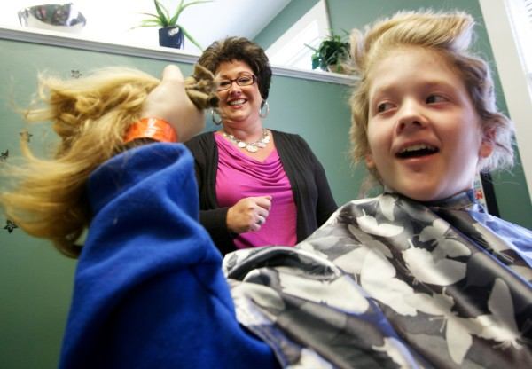 Josh Demers, 12, shows off his hair after stylist Amy Fabus cut it off for Locks of Love, an organization that makes wigs for cancer patients. Demers was originally growing his hair in hopes of giving it to a family friend, Angela Black, but she died of cancer just before her 40th birthday in 2012.