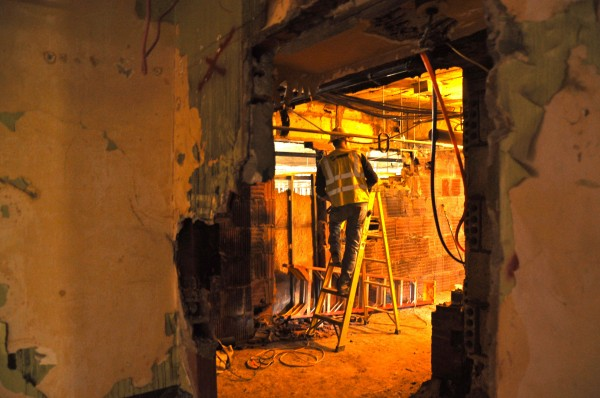 A worker is seen through a hole in the wall in the depths of the Eastland Park Hotel in Portland, which is being gutted and will reopen in December 2013 as the Westin Portland Harborview Hotel.