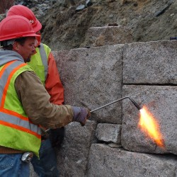 A construction worker uses a torch to remove irregularities and reshape a granite block used in rebuilding a more than century old sea wall protecting the Maine Sea Coast Mission property in Bar Harbor.