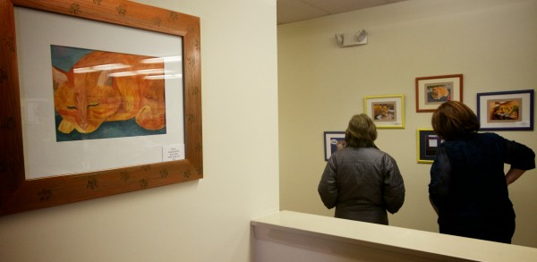 Two women look at art work inspired by Simba the cat in the Wesbrook school superintendent's office Thursday. Simba has hung around the high school for 13 years. The painting at left is &quotSleeping Simba&quot by student Kim Larlee.