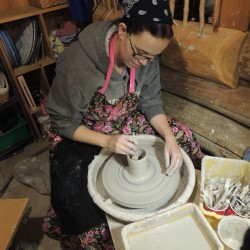 Shawna Mayo sits at her potter's wheel in her studio in Wallagrass.