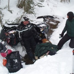 Phil Corriveau (left) of Fort Kent and Warden Adrian Marquis tend to Paul Lessard on Wednesday morning in St. John Plantation after the 64-year-old snowmobiler was found trapped under his overturned sled in a ditch just off the trail.
