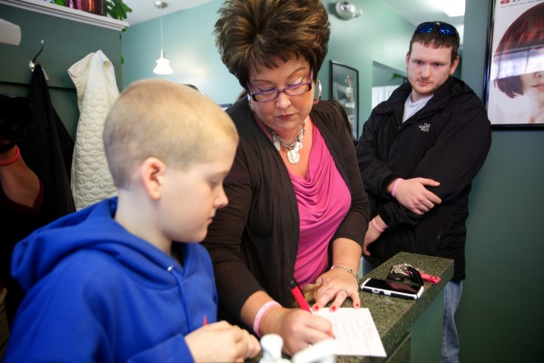 Josh Demers, 12, gives his name and address to stylist Amy Fabus in Bath Friday as he donates his long hair to Locks of Love, and organization that makes wigs foe cancer patients. Demers originally hoped to give his hair to family friend Angela Black, who died of cancer in 2012. Her son, Matt, (right) was on hand to watch Demers make his donation.